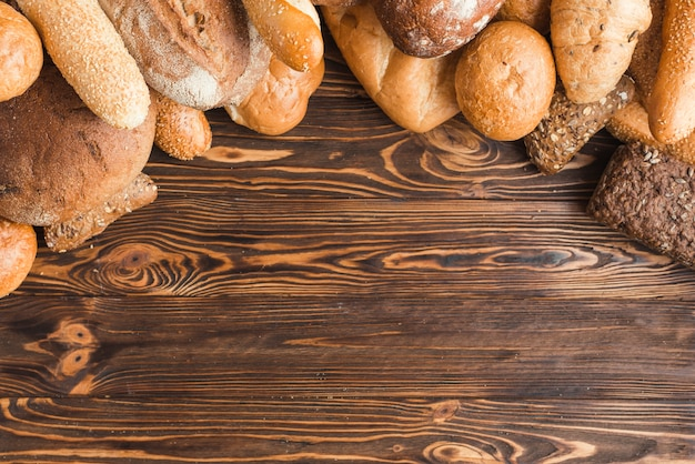 Overhead view of various breads on wooden background Free Photo