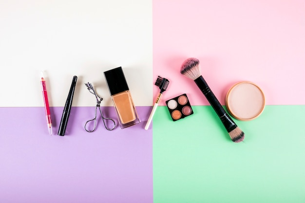 Overhead view of various cosmetic products on multi colored background Free Photo