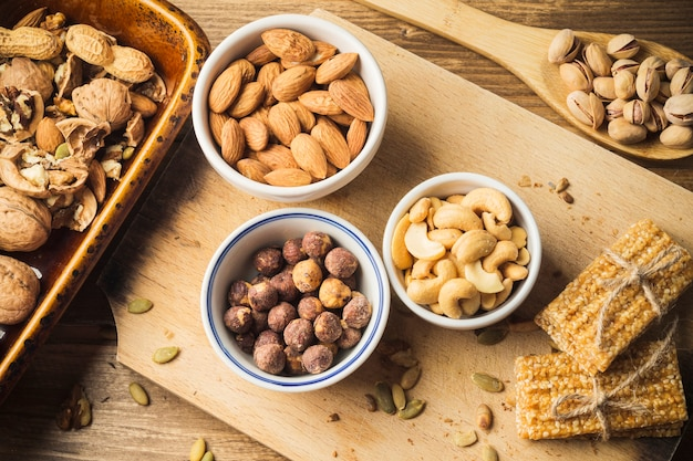 An overhead view of various dried fruits and energy bar on chopping board Free Photo