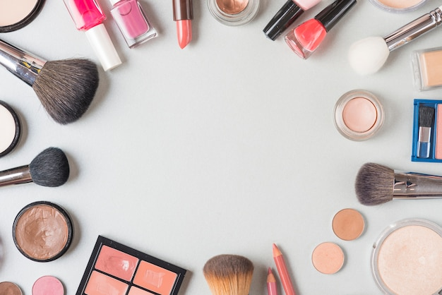Overhead view of various makeup products forming circular shape on white background Free Photo
