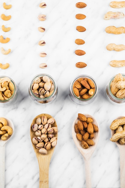 Overhead view of various nut food on marble backdrop Free Photo