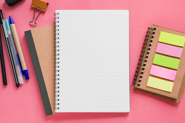 Overhead view of various stationeries on pink background Free Photo