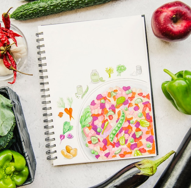 An overhead view of a vegetable and recipe book Free Photo