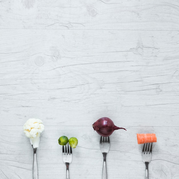 An overhead view of vegetables on fork arranged on wooden table Free Photo
