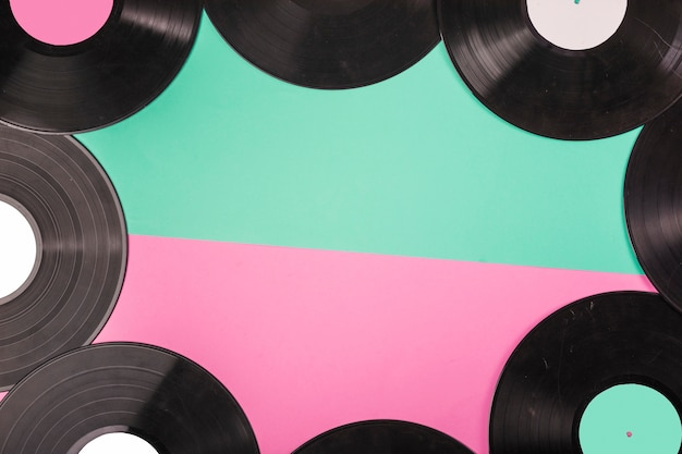 An overhead view of vinyl records border on dual green and pink background Free Photo
