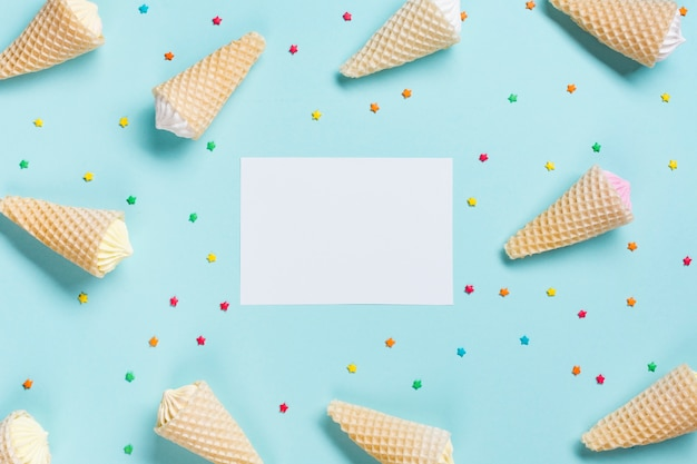 An overhead view of waffle cones and sprinkles surrounded near the white blank paper on blue backdrop Free Photo