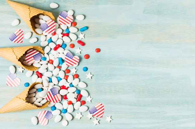 An overhead view of waffle cones with spilled candies and heart shape usa flag on blue backdrop Free Photo