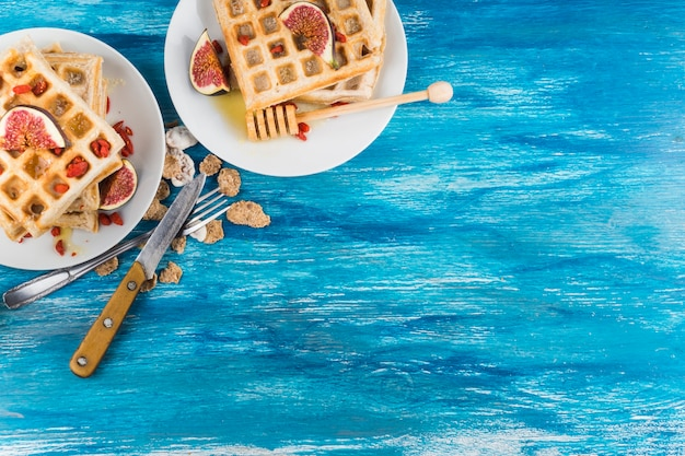 An overhead view of waffles with fig slices on plate against wooden blue textured background Free Photo
