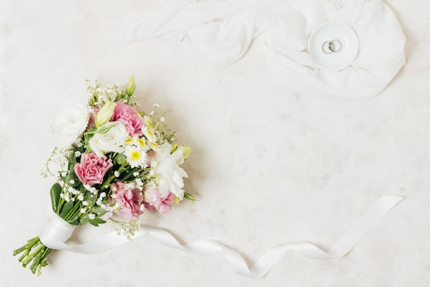 An overhead view of wedding rings on plate over scarf near the flower bouquet Free Photo