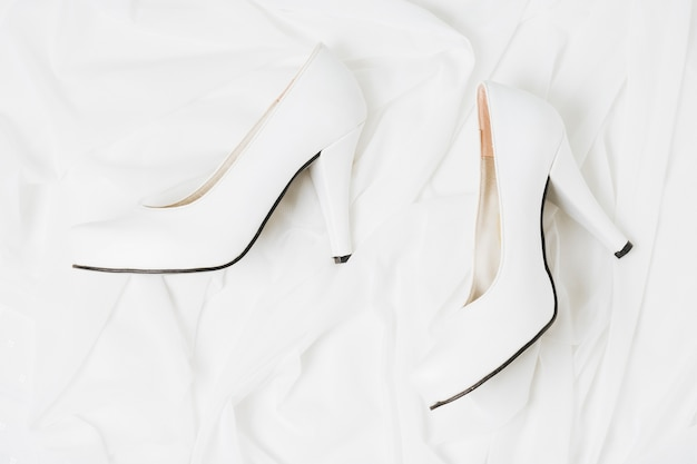 An overhead view of wedding white high heels on white cloth Free Photo