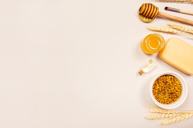 Overhead view of wheat ears; bee pollen; essential oil; soap; honey; honey dipper and makeup brush Free Photo