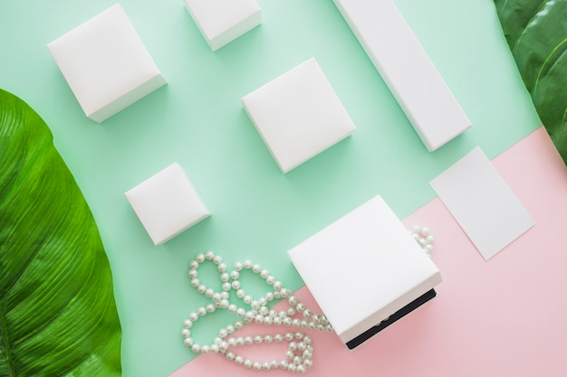 Overhead view of white boxes with pearls and leaf on colored background Free Photo