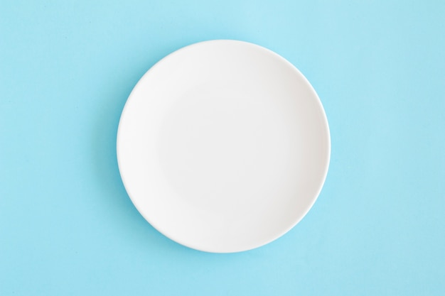 Overhead view of white empty plate on blue background Premium Photo