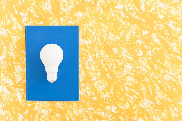 Overhead view of white light bulb on blue notebook over the pattern background Free Photo