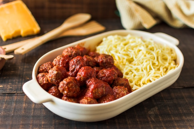 An overhead view of white lunchbox filled with meatballs and trenette pasta Free Photo