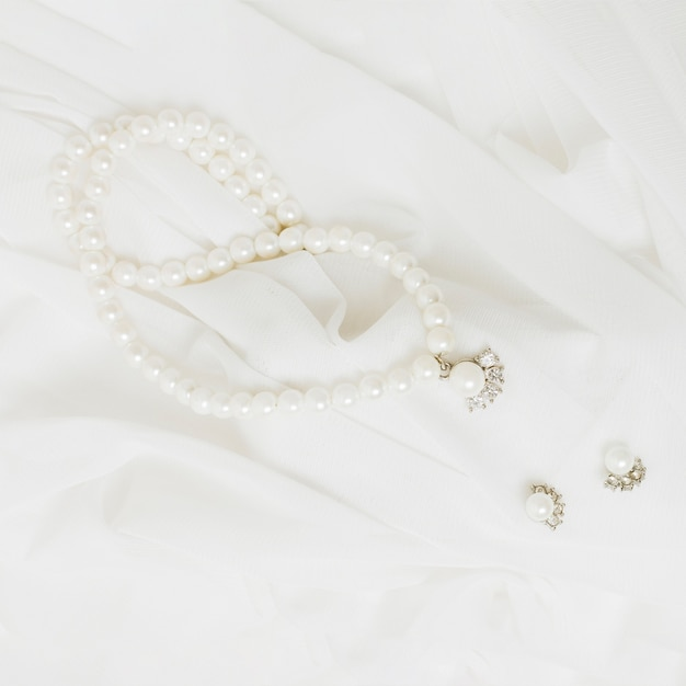 An overhead view of white pearls necklace and earrings on white scarf Free Photo
