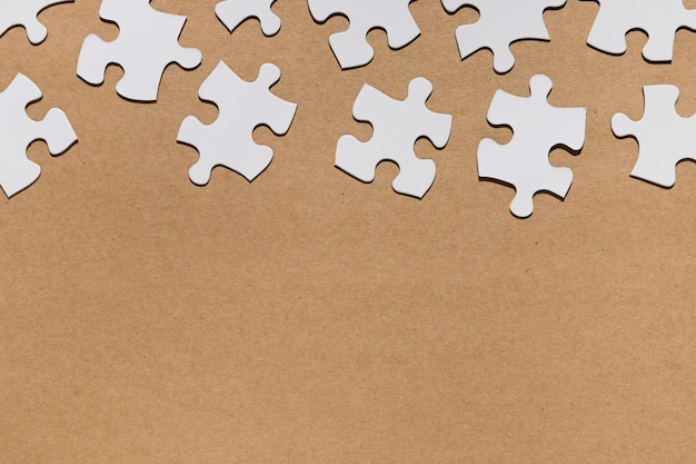 Overhead view of white puzzle pieces on brown paper textured Free Photo