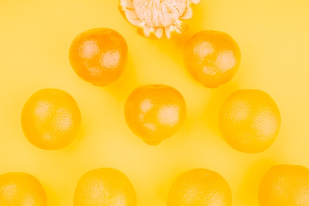 An overhead view of whole oranges on yellow backdrop Free Photo