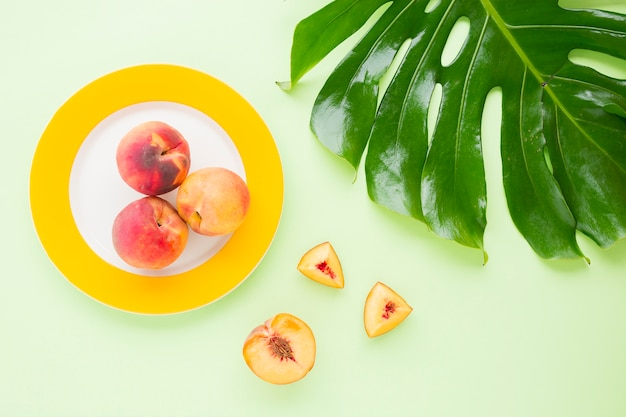 An overhead view of whole peach on plate with slices and green monstera leaf on pastel backdrop Free Photo