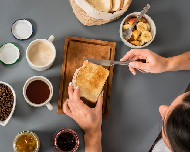 An overhead view of woman applying jam on bread with butter knife on grey backdrop Free Photo