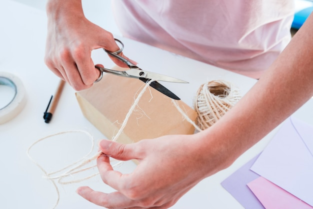 An overhead view of a woman cutting the jute thread with scissor on table Free Photo