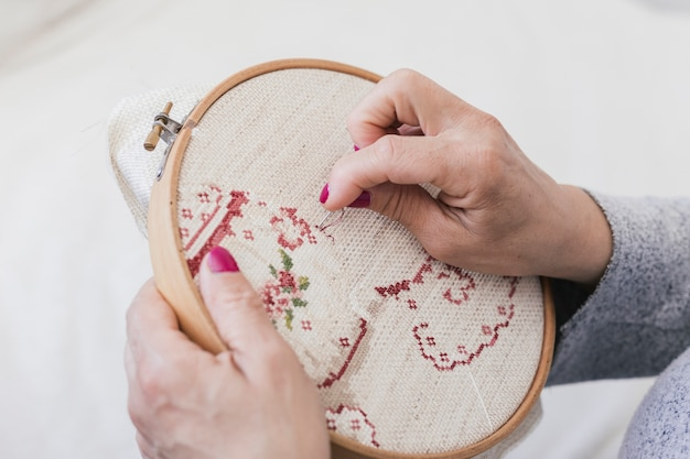 An overhead view of woman embroidering on cross stitching hoop with needles Premium Photo