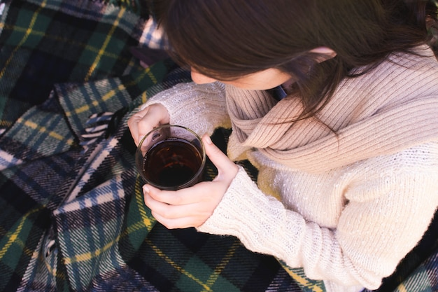 An overhead view of a woman holding herbal tea cup in hand Free Photo