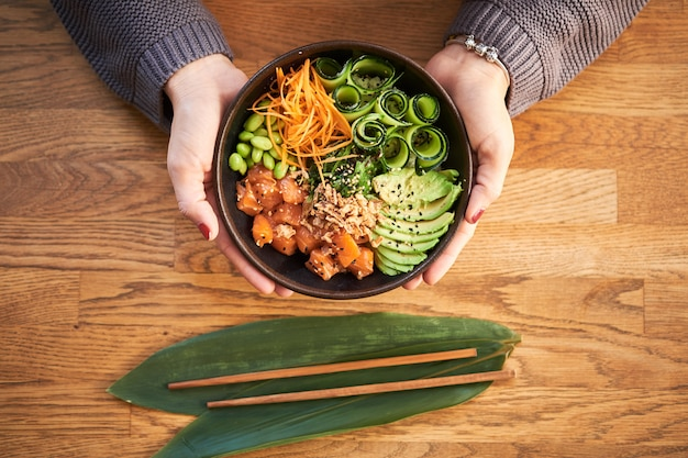 Overhead view of woman holding traditional hawaiian dish poke bowl in hands on wooden . hawaiian and japanese cuisine. healthy food. Premium Photo