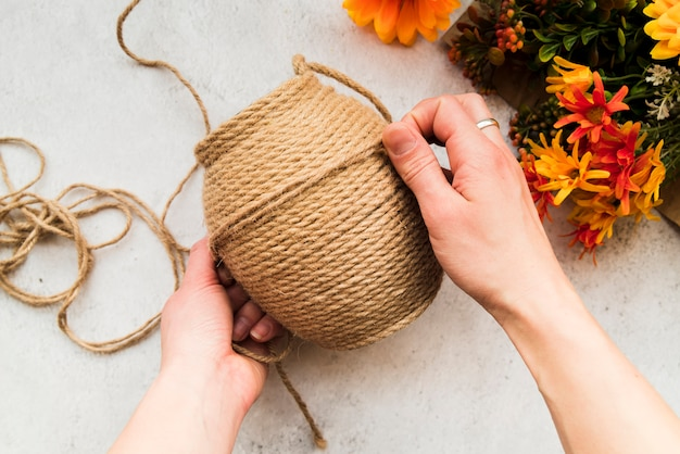 An overhead view of a woman making the string with jute string on textured backdrop Free Photo