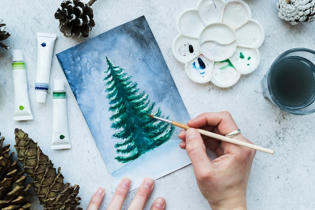 An overhead view of a woman's hand painting christmas tree on canvas Free Photo