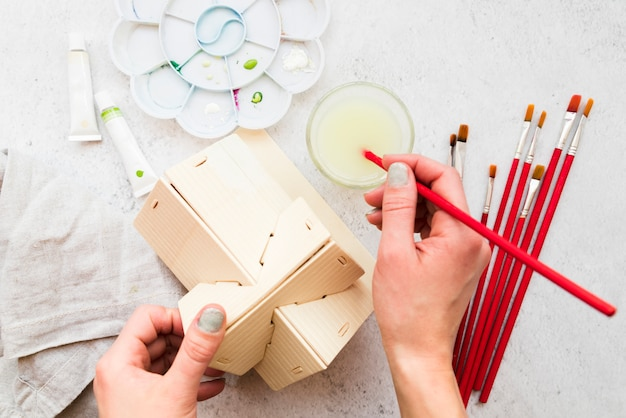 An overhead view of woman's hand painting the wooden house model with paintbrush Free Photo