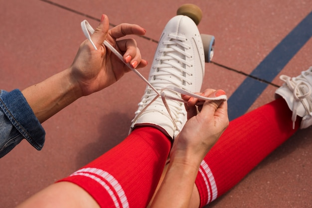 An overhead view of a woman sitting on ground tying the lace of roller skate Free Photo