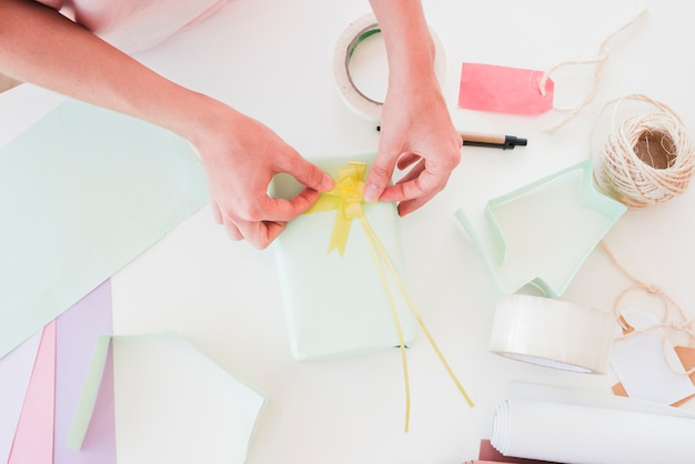 An overhead view of woman sticking yellow ribbon on wrapped gift box Free Photo