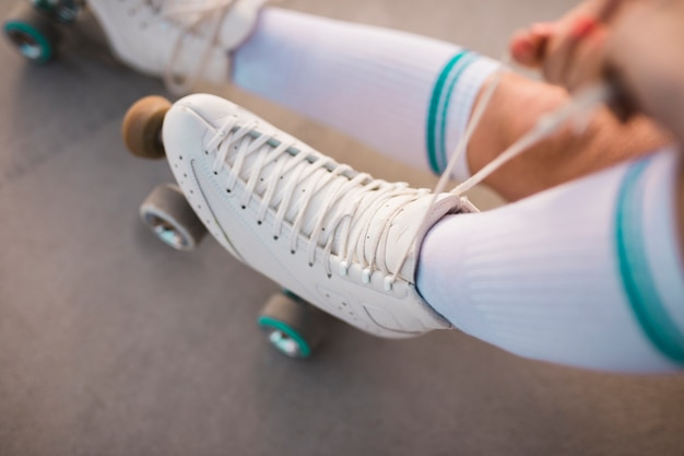 An overhead view of a woman tying roller skate lace Free Photo