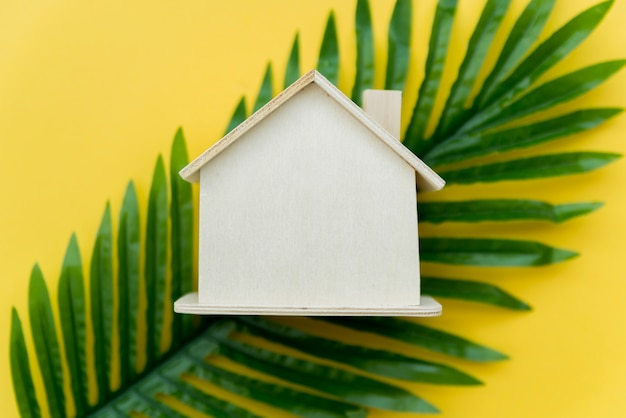An overhead view of wooden house over the green leaves against yellow background Free Photo