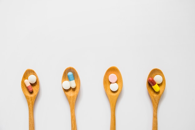 Overhead view of wooden spoons with pills isolated on white background Free Photo