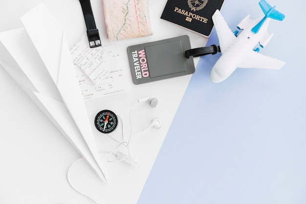 An overhead view of world traveler tag with passport; paper airplane; map; compass; tickets; toy airplane and earphone on dual background Free Photo