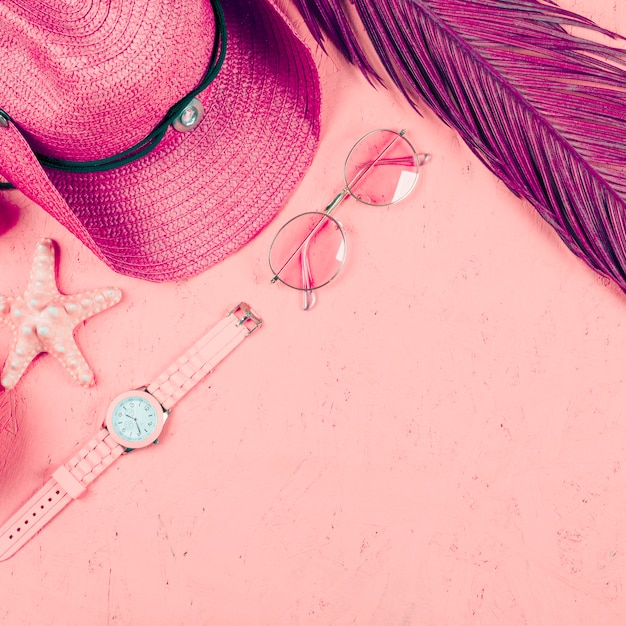 An overhead view of wristwatch; sunglasses; hat; leaf and starfish on pink textured backdrop Free Photo