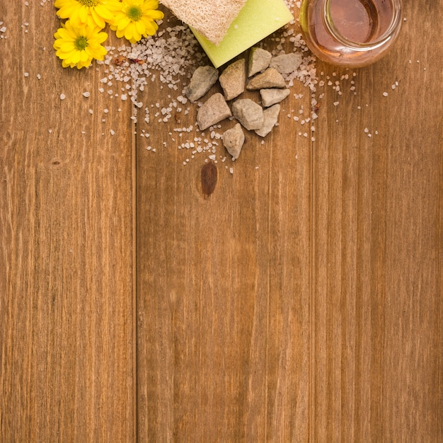 An overhead view of yellow flowers; salt; stones; sponge; loofah and honey bottle on wooden textured background Free Photo