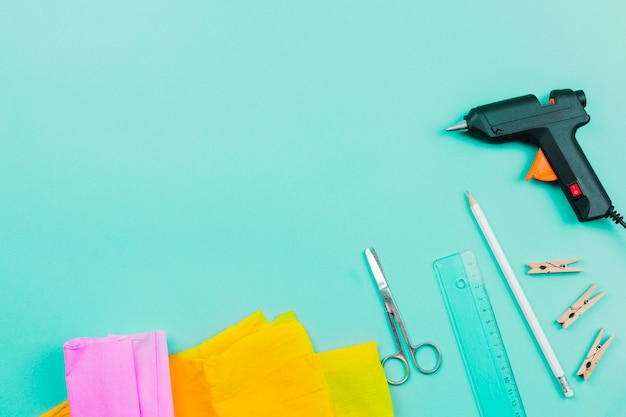 An overhead view of yellow and pink paper; scissor; ruler; pencil; clothespins and electric glue gun on turquoise background Free Photo