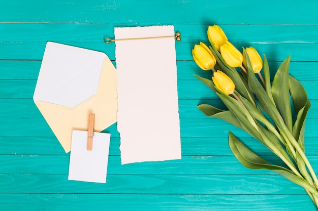 Overhead view of yellow tulip flowers; blank paper; and open envelope above green backdrop Free Photo