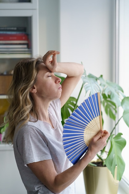 Overheated woman in t-shirt using wave fan suffer from heat sweating, cools herself, feels sluggish Premium Photo