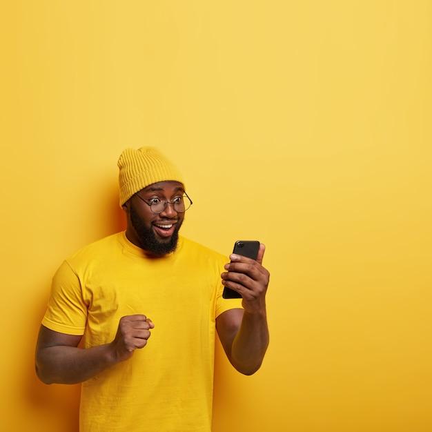太い毛で大喜びのアフロマン、携帯電話を楽しく見て、明るい気分で、良いニュースを祝い、くいしばられた握りこぶしを保ち、黄色のスタイリッシュな帽子をかぶっています 無料写真