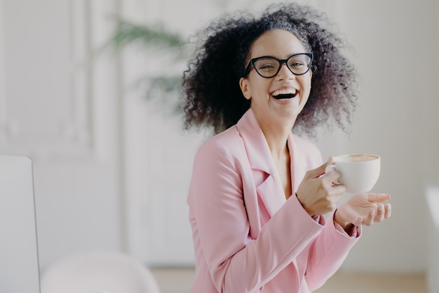 Overjoyed curly haired woman laughs happily while drinks hot coffee Premium Photo