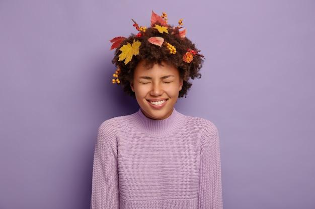 La donna riccia felicissima ride positivamente, ha umore autunnale, sorride ampiamente, scherza con gli amici, ha foglie d'acero gialle e bacche di sorbo nei capelli, vestita in abbigliamento casual. felicità, benessere Foto Gratuite