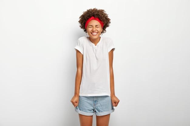 아프로 머리를 가진 기뻐서 어두운 피부를 가진 여자는 주먹으로 손을 꽉 쥐고 캐주얼 한 여름 옷을 입고 오랫동안 기다려온 휴가를 즐기고 흰색 배경에 고립 된 좋은 감정을 표현합니다. 무료 사진