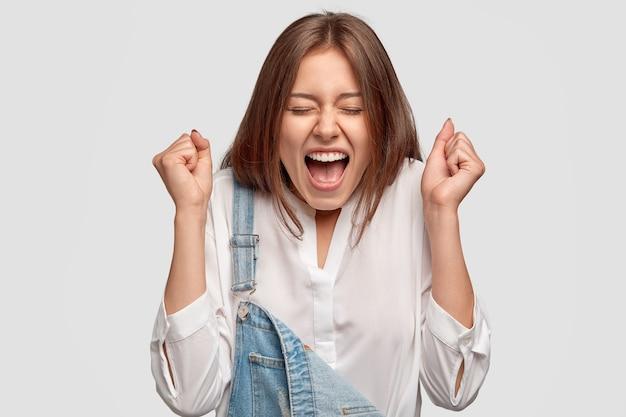 大喜びの女の子は大きな幸せで拳を食いしばり、大声で叫び、仕事での成功を祝います 無料写真