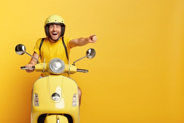 Overjoyed guy with helmet driving yellow scooter Free Photo