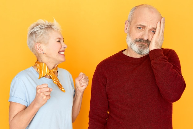 Overjoyed happy middle aged woman with blonde pixie hair clenching fists in excitement winning in lottery, her sad upset senior husband with beard holding hand on his cheek, having depressed look Free Photo