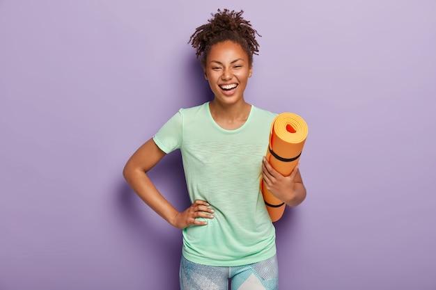 L'atleta femminile dalla pelle scura e sana, felicissima, tiene la mano sui fianchi, tiene il tappetino arrotolato, è in buona forma fisica, si allena tutti i giorni, indossa maglietta e leggings. persone, yoga Foto Gratuite
